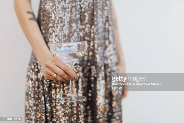 midsection of woman with drink standing against white background - silver dress stock pictures, royalty-free photos & images