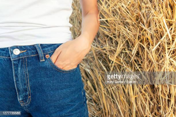 midsection of woman with hand in pocket against hay bale - mains dans les poches photos et images de collection