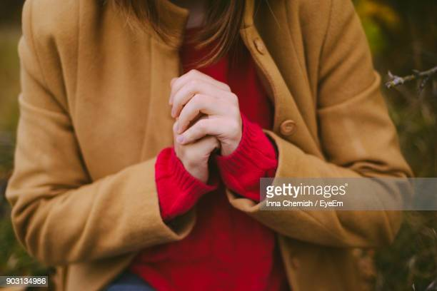 midsection of woman with hands clasped sitting on field - mani incrociate foto e immagini stock