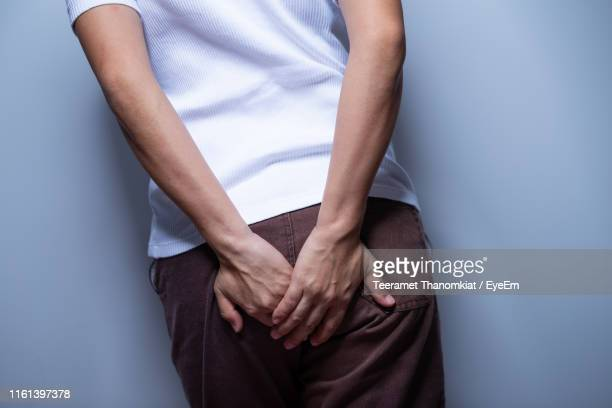 midsection of woman with hands on buttocks standing against gray background - culos fotografías e imágenes de stock