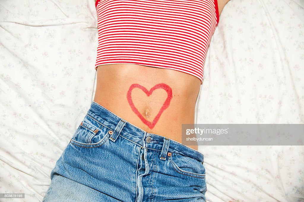 Midsection of woman with heart drawing on stomach : Stock Photo