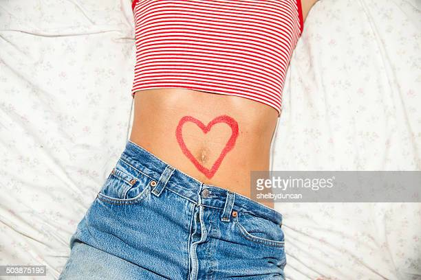 Midsection of woman with heart drawing on stomach