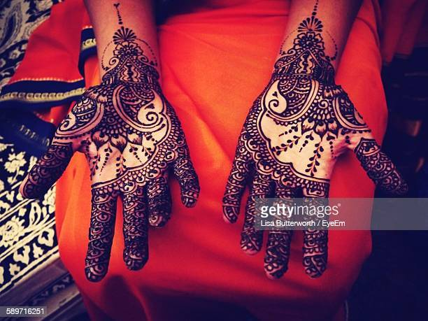 Midsection Of Woman With Henna Tattoo On Hands