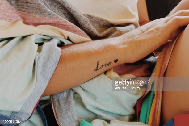 midsection of woman with love tattoo on hand - tattoo designs hearts stock pictures, royalty-free photos & images