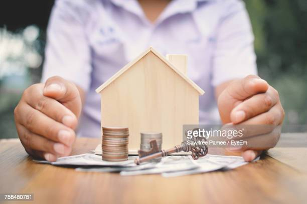 Midsection Of Woman With Model House And Currencies On Table