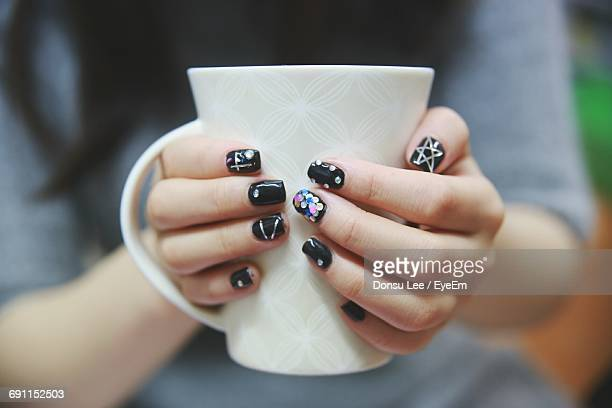 Midsection Of Woman With Nail Art Holding Cup