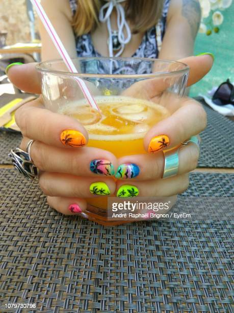 midsection of woman with nail art holding drink on table - nail art stock pictures, royalty-free photos & images