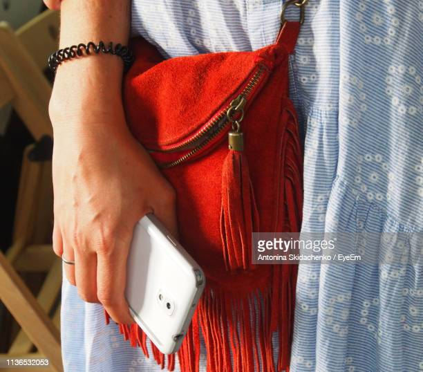 Midsection Of Woman With Red Bag And Mobile Phone Standing Outdoors