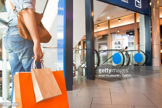 Midsection Of Woman With Shopping Bags Standing In Shopping Mall