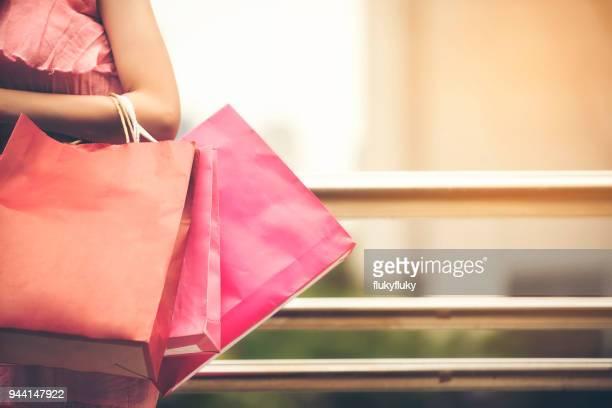 midsection of woman with shopping bags standing outdoors - bolsa rosa - fotografias e filmes do acervo