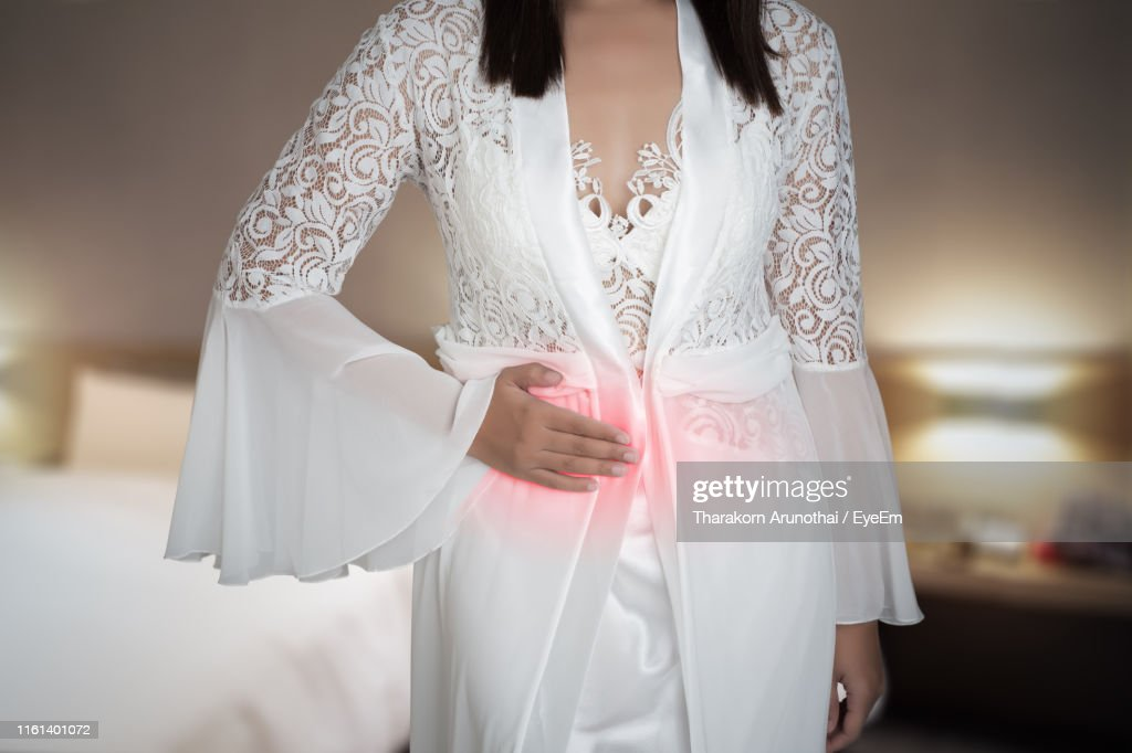 Midsection Of Woman With Stomachache Standing At Home : Stock Photo