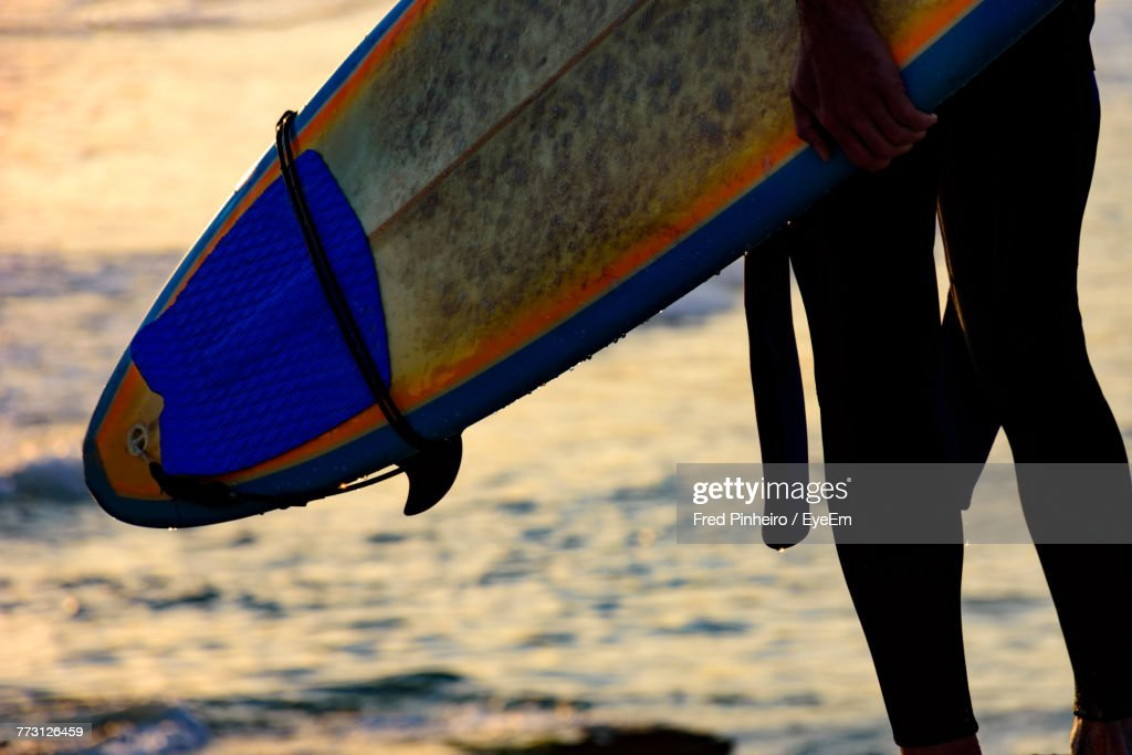 Midsection Of Woman With Surfboard At Beach : Photo