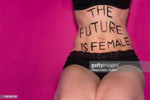 midsection of woman with text on her abdomen sitting against pink background - festa della donna foto e immagini stock