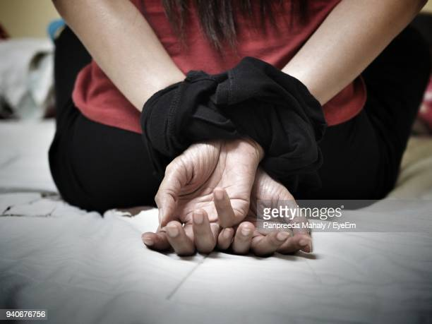 midsection of woman with tied hands on bed at home - frau gefesselt stock-fotos und bilder