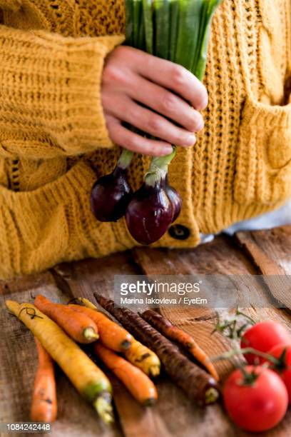 Midsection Of Woman With Vegetables At Table