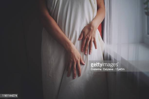 midsection of woman with white clothing standing at home - at home ストックフォトと画像