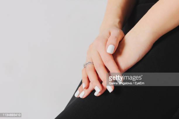 midsection of woman with white nail polishes with gray background - white nail polish stock pictures, royalty-free photos & images