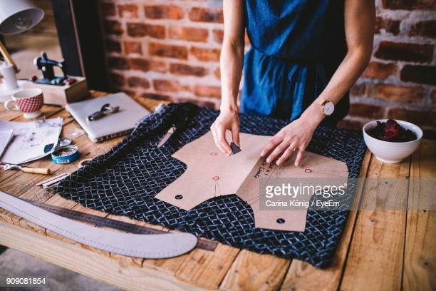 midsection of woman working at table in workshop - fashion designer stock photos and pictures