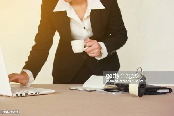 Midsection Of Woman Working At Table