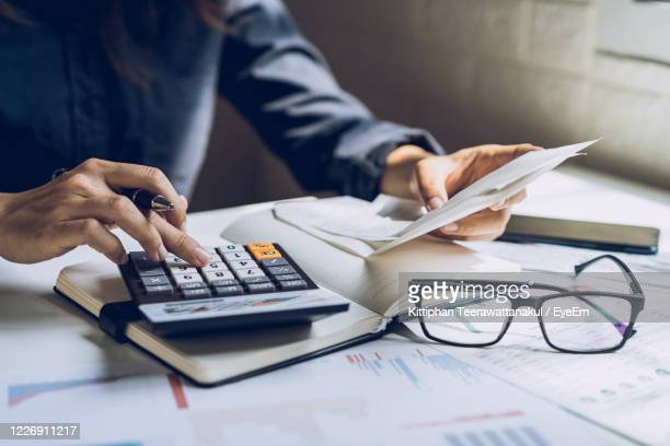 midsection of woman working in office - budget stock pictures, royalty-free photos & images