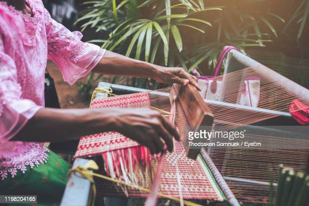 midsection of woman working on loom in factory - loom stock pictures, royalty-free photos & images
