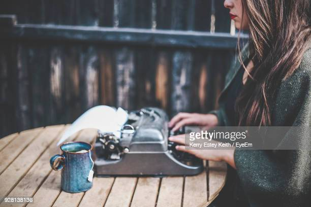 Midsection Of Woman Working On Typewriter Over Table