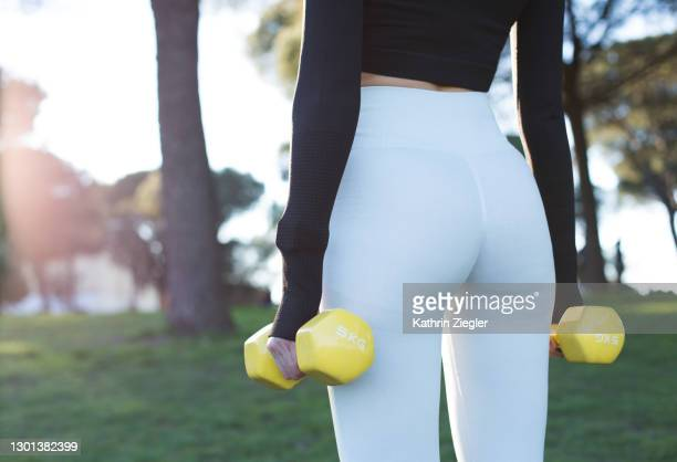 midsection of woman working out in the park, using weights - buttocks stock pictures, royalty-free photos & images