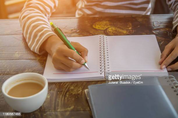 midsection of woman writing in book on table - 人体部位 ストックフォトと画像