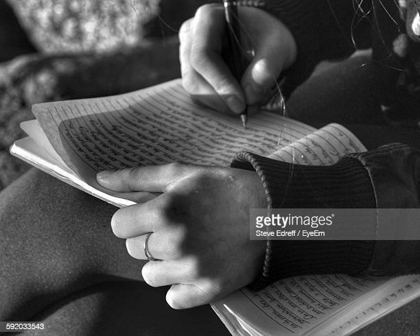 Midsection Of Woman Writing In Book