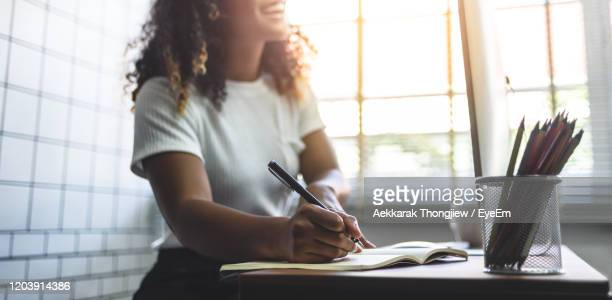midsection of woman writing in book while sitting on table - écrire photos et images de collection