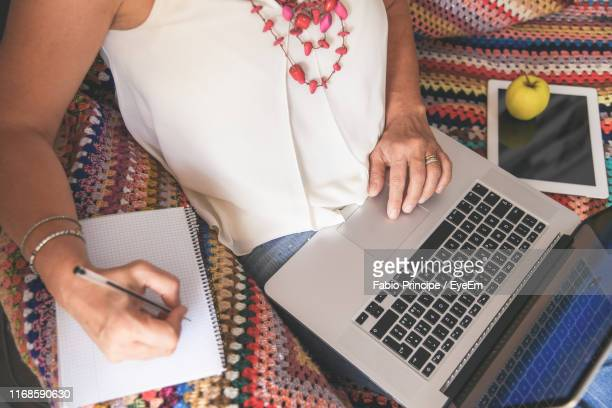 midsection of woman writing in book while using laptop at home - mittlerer teil stock-fotos und bilder