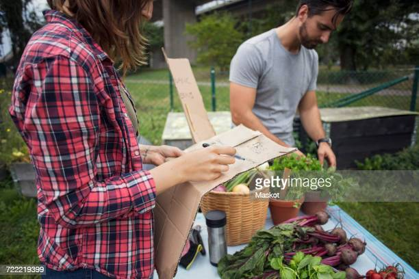 Midsection of woman writing on cardboard with man working in background at vegetable garden