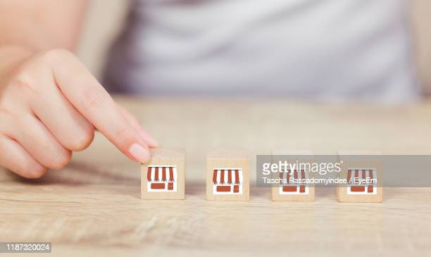 midsection of women arranging wooden blocks with store symbol on table - franchising stock pictures, royalty-free photos & images