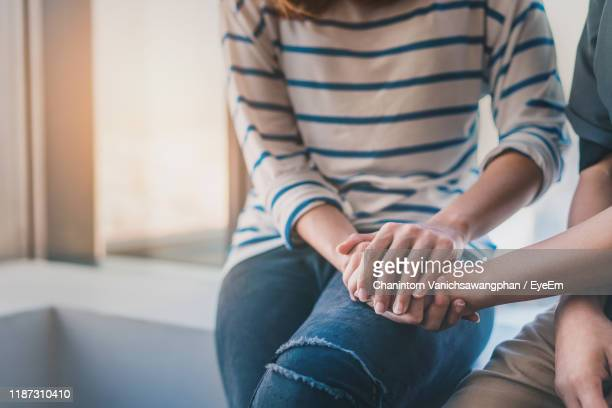 midsection of women consoling friend while sitting at home - välbefinnande bildbanksfoton och bilder
