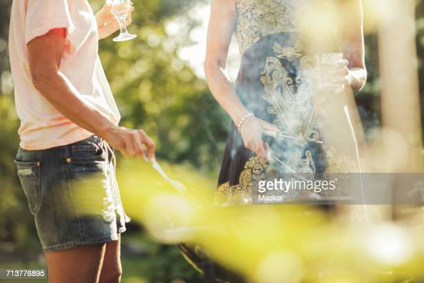 Midsection of women cooking on barbecue grill at back yard