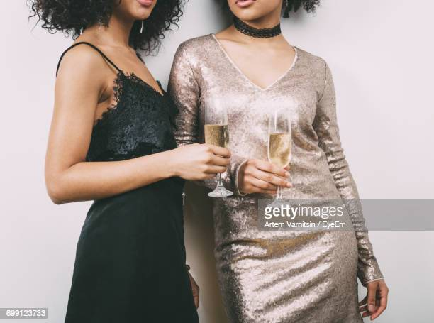 midsection of women holding champagne glasses - イブニングドレス ストックフォトと画像