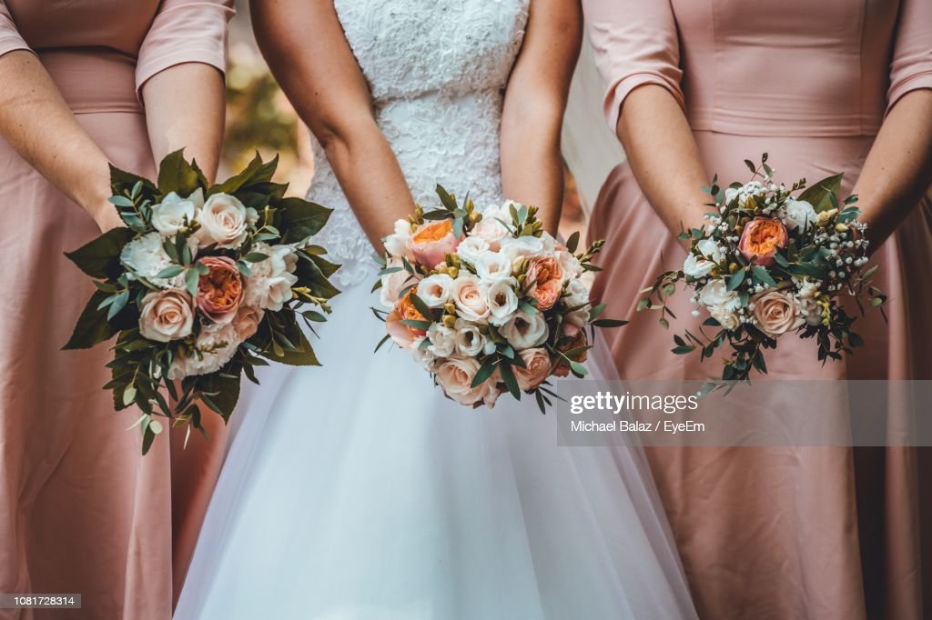 Midsection Of Women Holding Flower Bouquets In Wedding Ceremony : Stock Photo