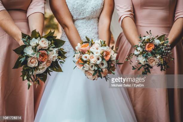 midsection of women holding flower bouquets in wedding ceremony - bridesmaid stock pictures, royalty-free photos & images
