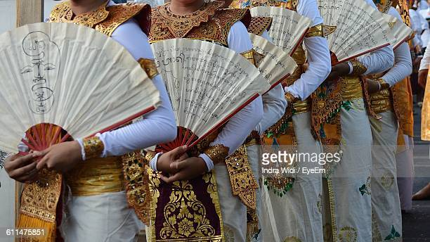 midsection of women holding folding fans - balinese culture stock pictures, royalty-free photos & images