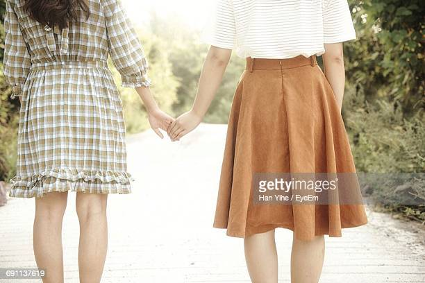 midsection of women holding hands on road - up skirt stock photos and pictures