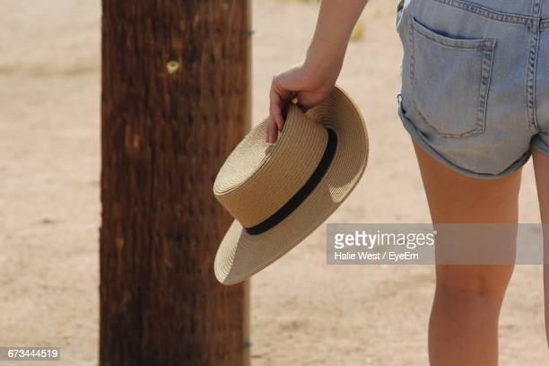 Midsection Of Women Holding Hat At Beach