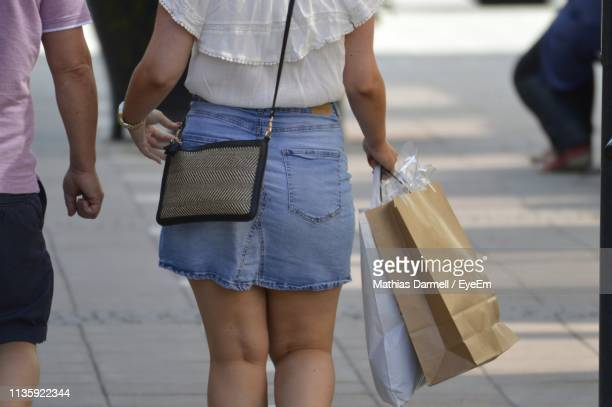 midsection of women holding shopping bags while walking on footpath in city - minirok stockfoto's en -beelden
