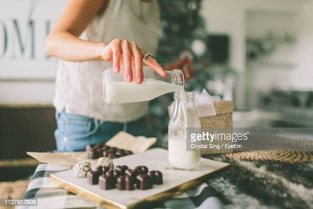 midsection of women pouring milk - milk stock pictures, royalty-free photos & images