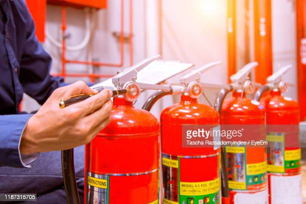 midsection of worker checking fire extinguishers with pen at factory - fire extinguisher stock pictures, royalty-free photos & images