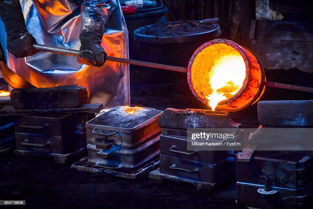 Midsection Of Worker Pouring Cast Iron In Container At Still Mill : Stock Photo