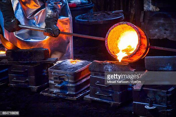 midsection of worker pouring cast iron in container at still mill - steelmaking stock photos and pictures