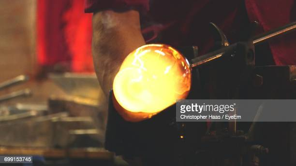 Midsection Of Worker With Molten Glass In Workshop