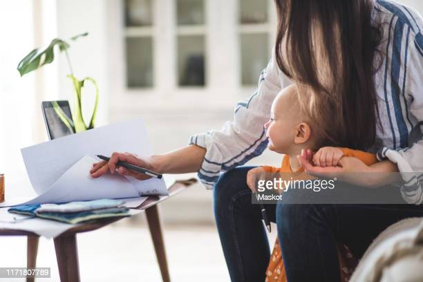 midsection of working mother examining documents with baby girl at home office - working mother stock pictures, royalty-free photos & images