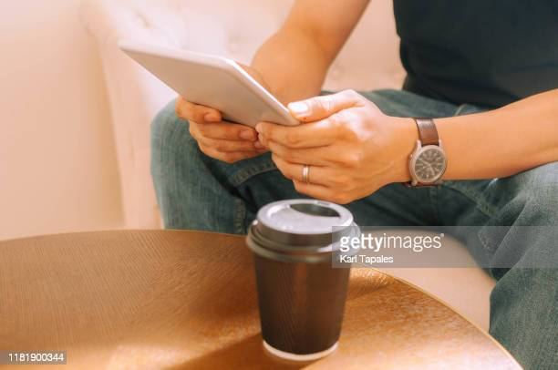 a midsection of young asian man is using a smartphone indoor while drinking hot coffee from a disposable coffee cup - daily life in philippines stock pictures, royalty-free photos & images