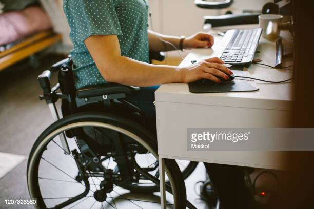 midsection of young disabled woman using computer at home - differing abilities fotografías e imágenes de stock
